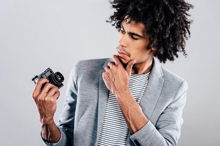 retro styled: How does this thing works? Handsome young African man holding retro styled camera and looking at it while standing against grey background