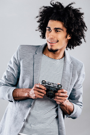 looking away from camera: Cheerful photographer. Handsome young African man holding retro styled camera and looking away with smile while standing against grey background Stock Photo