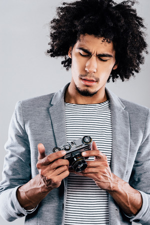 retro styled: Where is digital screen here? Handsome young African man holding retro styled camera and looking at it while standing against grey background Stock Photo