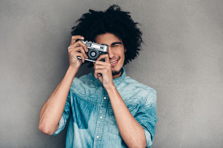 retro styled: Show me your best smile!Cheerful young African man holding retro styled camera and focusing on you while standing against grey background Stock Photo