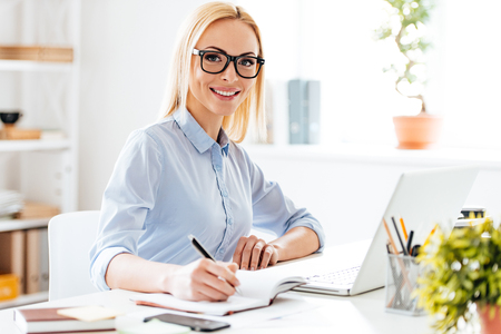 writing desk: Expertise in her business. Cheerful young beautiful woman making some notes and looking at camera with smile while sitting at her working place
