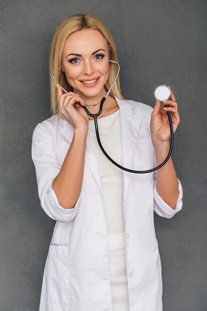 a lady doctor: Take off your shirt please! Beautiful young female doctor holding stethoscope and looking at camera with smile while standing against grey background