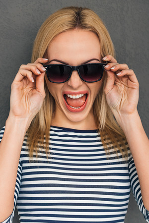 Furioso y emocional. Joven y bella mujer ajustando sus gafas de sol y mantener la boca abierta mientras está de pie contra el fondo gris
