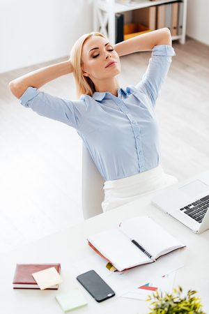 woman from behind: Little rest. Top view of beautiful young woman holding hands behind her head and keeping eyes closed while sitting at her working place Stock Photo