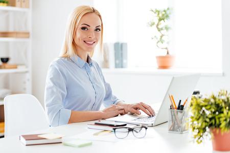 Hermosa empresaria. Alegre joven hermosa mujer que trabaja en la computadora portátil y mirando la cámara con sonrisa mientras está sentado en su lugar de trabajo
