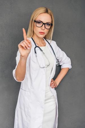 poner atencion: Prestar atención a esto! Hermosa mujer joven médico presionando sobre screenand digitales abandonada mirando al camerawhile pie contra el fondo gris Foto de archivo