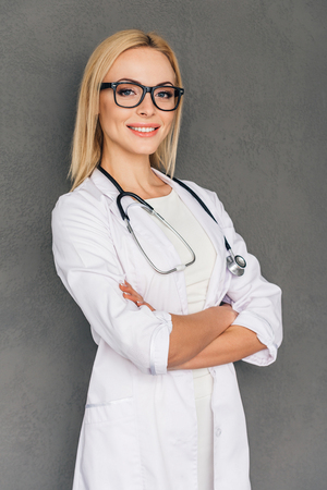 a lady doctor: She can cure you. Beautiful young female doctor keeping arms crossed and looking at camera with smile while standing against grey background