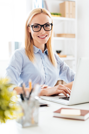 beautiful businesswoman: Elegant and cheerful businesswoman. Cheerful young beautiful woman in glasses looking at camera with smile while sitting at her working place Stock Photo