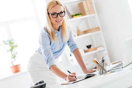 Let me write down it!Beautiful woman making some notes and looking at camera with smile while leaning to the table in office