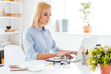 working desk: Searching for new solution. Pensive young beautiful woman working on laptop while sitting at her working place Stock Photo