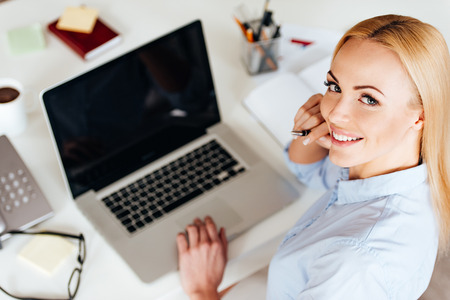 view woman: Beauty at work. Top view of cheerful young beautiful woman working on laptop and looking at camera with smile while sitting at her working place Stock Photo