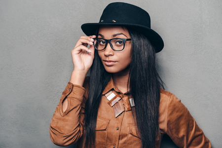 portrait of woman: Stylish look. Portrait of beautiful young African woman adjusting her glasses and looking at camera while standing against grey background