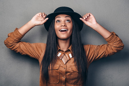 Her look is so stylish. Beautiful young cheerful African woman in hat looking up and smiling while standing against grey background