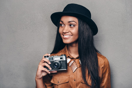 looking away from camera: Beautiful photographer. Beautiful cheerful young African woman holding retro styled camera and looking away with smile while standing against grey background Stock Photo