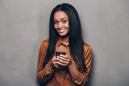 negras africanas: Mensaje de un amigo. Joven y bella mujer africana sosteniendo el teléfono inteligente y mirando la cámara mientras está de pie contra el fondo gris Foto de archivo