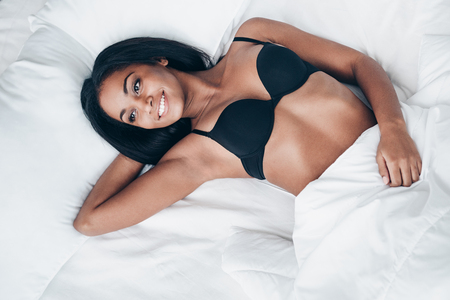 sex tenderness: Cheerful beauty in bed. Top view of beautiful young African woman in black lingerie lying in bed with smile
