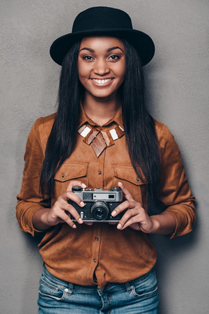 retro styled: Cheerful photographer. Beautiful cheerful young African woman holding retro styled cameraand looking at camera with smile while standing against grey background Stock Photo