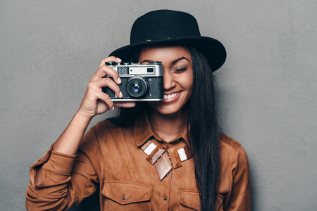 say cheese: Say cheese! Beautiful cheerful young African woman holding retro styled camera and focusing on you with smile while standing against grey background Stock Photo