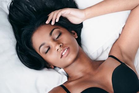femme noire nue: La belle au bois dormant. Vue de dessus close-up de la belle jeune femme africaine en lingerie noir couché dans son lit et de garder les yeux fermés