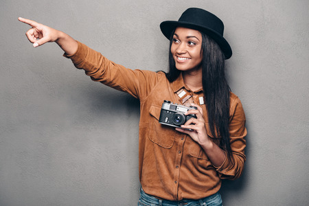retro styled: Lets take a picture there! Beautiful cheerful young African woman holding retro styled camera and pointing away with smile while standing against grey background