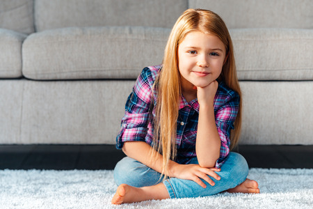 girl home: Maybe play? Cheerful little girl looking at camera with smile while sitting on the carpet in lotus position at home Stock Photo