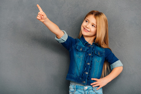 5 7: Take a look here! Cheerful littlegirl pointing away and smiling while standing against grey background