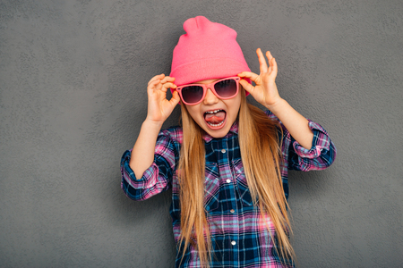 5 7: Cute and emotional. Beautiful little girl adjusting her sunglasses and keeping mouth open while standing against grey background Stock Photo