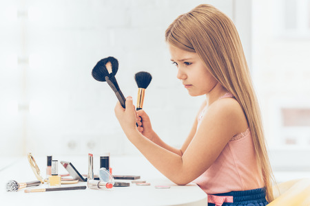 dressing table: Is this brush for contouring? Side view of pensivelittle girl choosing one of two make-up brushes while sitting at the dressing table Stock Photo
