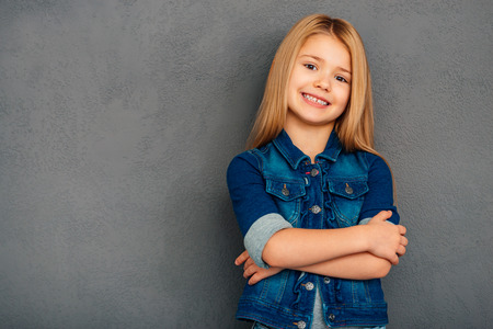 cutie: Little cutie. Cheerful little girl holding arms crossed and looking at camera with smile while standing against grey background