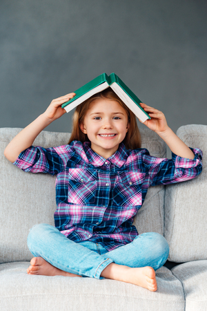 5 7: Lets play hide and seek! Cheerful little girl holding book over her head and looking at camera with smile while sitting on the couch in lotus position at home