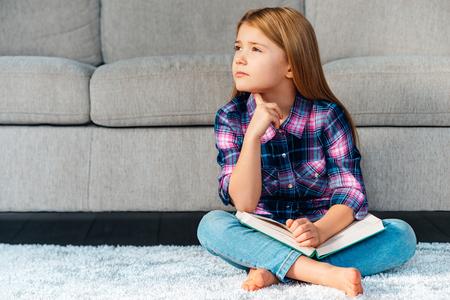 piedi nudi di bambine: Così tante domande. Pensieroso bambina azienda libro e guardando riflessivo, seduti sul tappeto nella posizione del loto a casa Archivio Fotografico