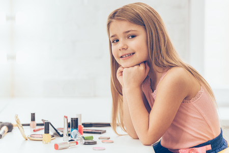 blond girl: My make-up is on point today! Side view of cheerful little girl keeping hands on chin and looking at camerawith smile while sitting at the dressing table
