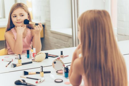 dressing table: My cheekbones on point today! Cheerful little girl applying make-up and looking at her reflection in mirror while sitting at the dressing table