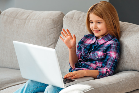 waving: Hello grandma! Beautiful little girl using her laptop and waving with her hand while sitting on the couch at home