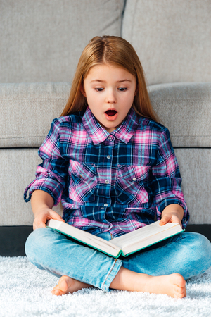 little girl surprised: No way! Beautiful little girl reading book and looking surprised while sitting on the carpet in lotus position at home