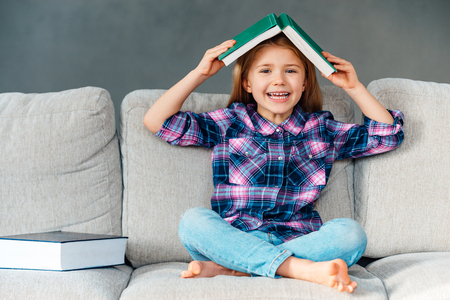 assimilate: Knowledge assimilate better this way! Cheerful little girl holding book over her head and looking at camera with smile while sitting on the couch in lotus position at home Stock Photo