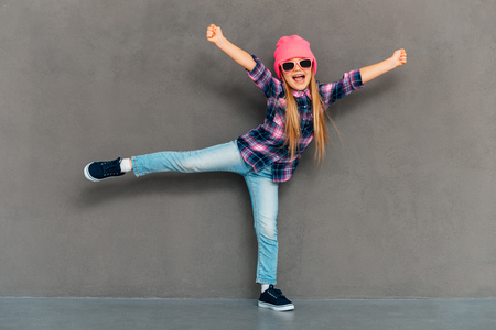 one child: Pure joy. Full length of cheerful little girl in sunglasses keeping arms outstretched and looking at camera with smile while standing on one leg against grey background