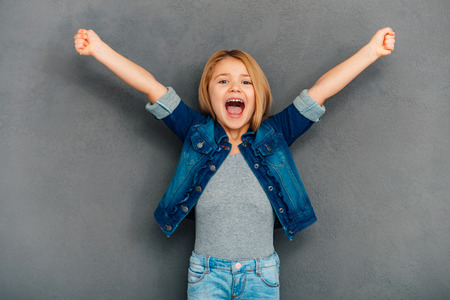 5 7: Hurray! Cheerful little girl keeping arms outstretched and looking at camera while standing against grey background Stock Photo