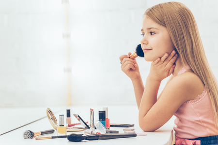Adding some color to my cheeks. Side view of cheerful little girl applying make-up and looking at her reflection in mirror while sitting at the dressing table