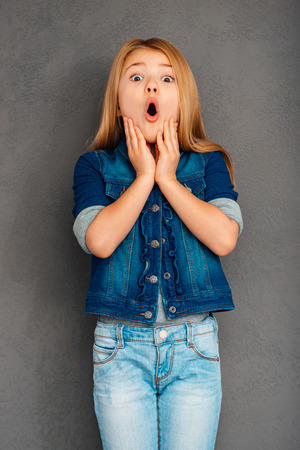camera girl: Oh no! Beautiful littlegirl keeping mouth open and looking surprised while standing against grey background