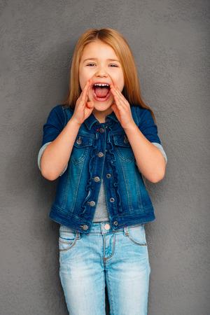 you can: puedes escucharme ahora? La niña alegre mantener la boca abierta y mirando a la cámara mientras está de pie contra el fondo gris