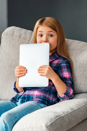 little girl surprised: Busted with her touchpad. Beautiful little girl holding her touchpad and looking surprised while sitting on the couch at home