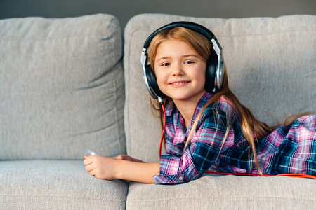 laying down: Spending great time at home. Beautiful little girl in headphones looking at camera with smile while lying on front on the couch at home