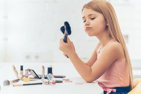 dressing table: Which brush should I choose? Side view of pensivelittle girl choosing one of two make-up brushes while sitting at the dressing table