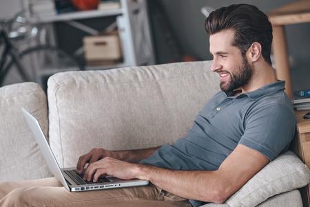 uomini belli: Digitando nuovo post sul blog. Vista laterale di giovane uomo usando il suo computer portatile con il sorriso, mentre seduto sul divano di casa Archivio Fotografico