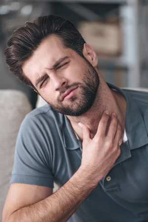 home keeping: Getting sick. Frustrated handsome young man touching his neck and keeping eyes closed while sitting on the couch at home