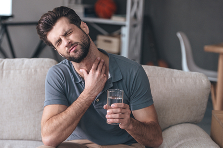 sore throat: Terrible pain in his throat. Frustrated handsome young man touching his neck and holding a glass of water while sitting on the couch at home