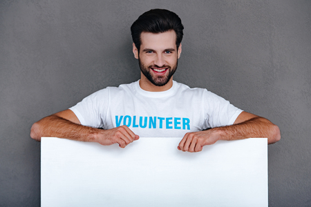 smile please: Please donate! Confident young man in volunteer t-shirt leaning to white board and looking at camera with smile while standing against grey background