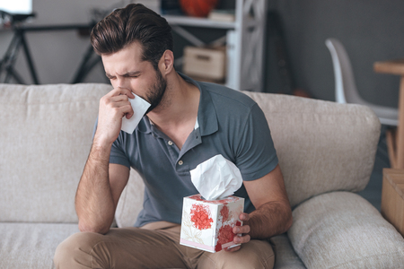 only one person: Terrible allergy. Frustrated handsome young man sneezing and using tissue while sitting on the couch at home Stock Photo