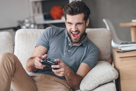 playing video game: That is my best round! Excited young handsome man playing video game and keeping mouth open while sitting on the couch at home Stock Photo